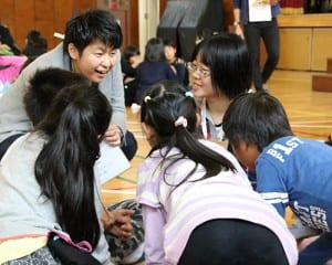 子どもたちと話す藥師代表理事とReBitメンバーの若者