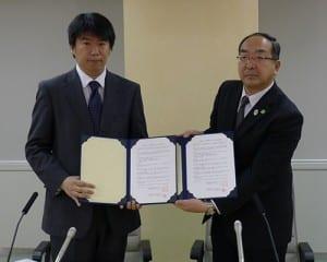 協定書を掲げる伊東指導部長(右)と江口室長