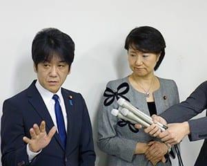 厳しい表情で報道陣の質問に答える義家副大臣と渡嘉敷副大臣