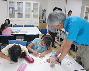 寺子屋先生に勉強を教えてもらう子どもたち