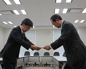 文科省の担当者に報告書を手渡す鈴木社長
