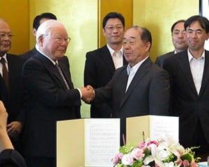 協定を結び握手を交わす西頭学長(左)と教員研修センターの高岡理事長