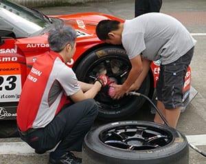 生徒がレーシングカーのタイヤ交換を体験