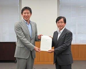 鈴木長官(左)に報告書を手渡す真田座長