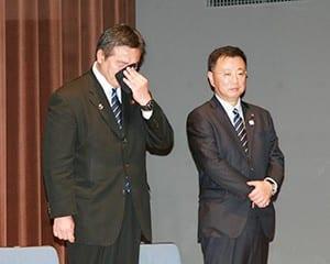 松野博一新文科相の隣で目を覆う馳前文科相(左)