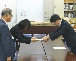 文科省の望月 禎教科書課長に調査報告書を提出した教育芸術社の市川かおり社長(奥)と大日本図書の戸川秀夫常務
