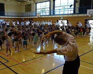 体操に挑戦する児童と石田校長