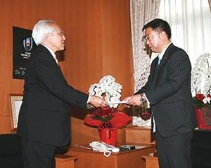 松野文科相に行動規範を提出する野澤会長(左)