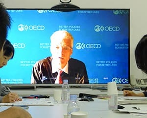 テレビ会議システムでOECD本部があるパリから日本の記者の質問に答えるシュライヒャー局長