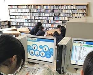 新聞で時事問題を調べる生徒
