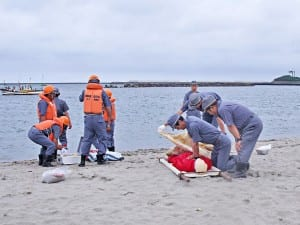 救助者を浜で心肺蘇生する訓練