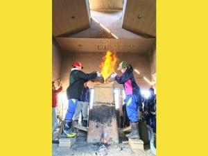 児童がたたらの炉の中に砂鉄と木炭を交互に入れてゆく
