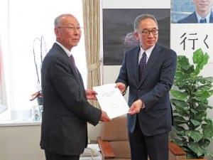 髙橋局長に報告書を手渡す森田座長(左)